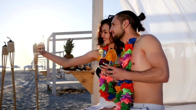 couple drink cocktail and take pictures on mobile phone, friends with wreath flowers on neck photographed on gadget video