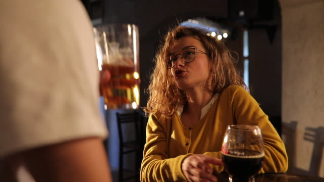 Couple drinking beer Beautiful happy couple drinking a beer at pub charming stock videos & royalty-free footage