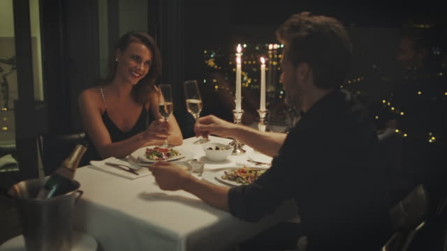 Couple drinking champagne Couple sitting at a dining table clinking their glasses and drinking champagne.   romance stock videos & royalty-free footage
