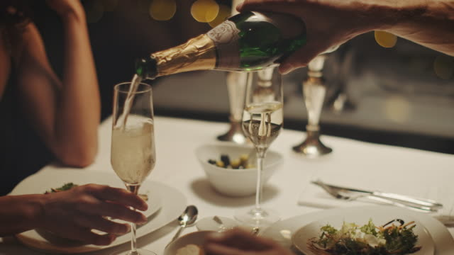stockvideo's en b-roll-footage met paar champagne drinken - restaurant table