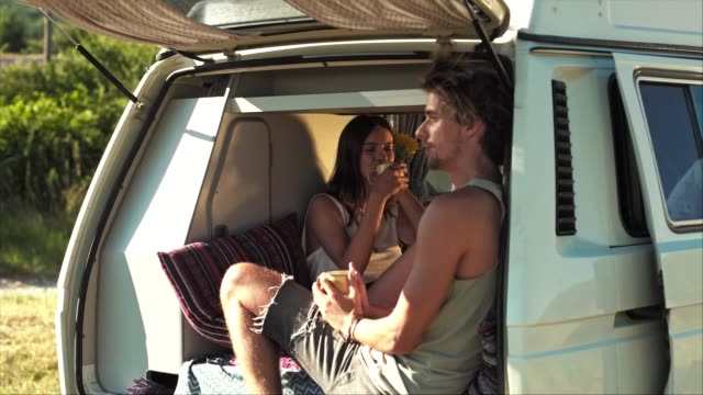 Couple drinking coffee in van during vacation