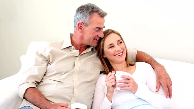 Couple drinking coffee on the couch video