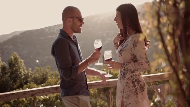 Couple drinking red wine on mediterranean rustic countryside house balcony video