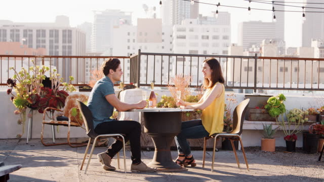 couple drinking wine and making toast on rooftop terrace with city skyline in background - terrazza video stock e b–roll