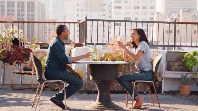 vidéos et rushes de couple, boire du vin et de faire le toast sur toit-terrasse avec des toits de la ville en arrière-plan - man drinking terrace