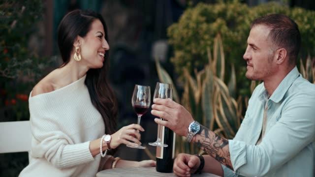 vidéos et rushes de couple de boire du vin et de grillage assis sur la terrasse à la maison - man drinking terrace