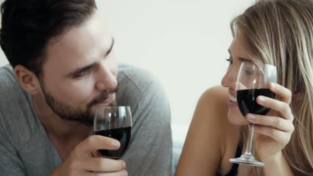 침실에서 와인을 마시는 커플 - 이성 커플 스톡 비디오 및 b-롤 화면