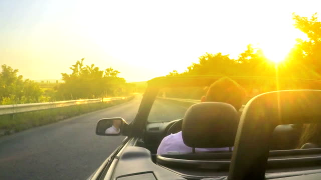 couple drive convertible car toward sunset - country fashion stock videos & royalty-free footage