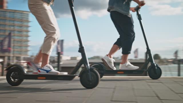 couple driving electric kick scooters in city - monopattino elettrico video stock e b–roll