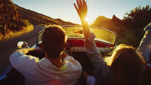 Couple Driving into the Sunset Driving into the sunset, romantic couple enjoying beautiful drive on country road love emotion stock videos & royalty-free footage