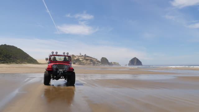 Couple driving off road vehicle driving on beach video