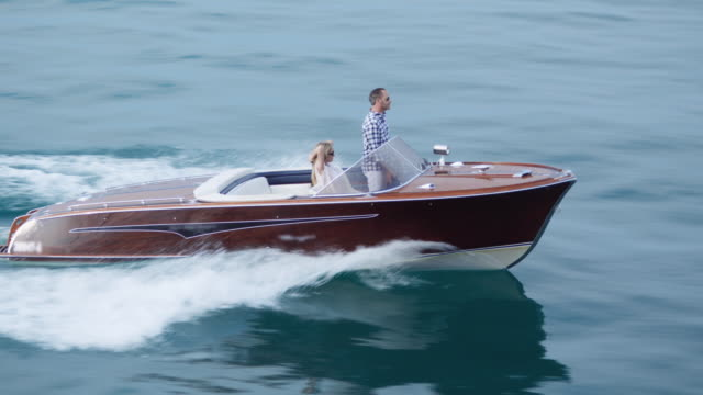 stockvideo's en b-roll-footage met couple driving on yacht - boat