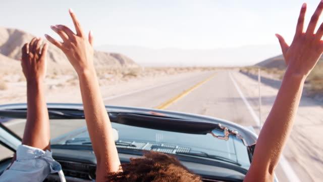 vídeos de stock e filmes b-roll de couple driving open top car raising their hands in the air - afro americano