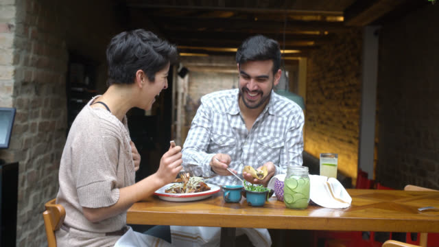 Couple eating at a Mexican restaurant video