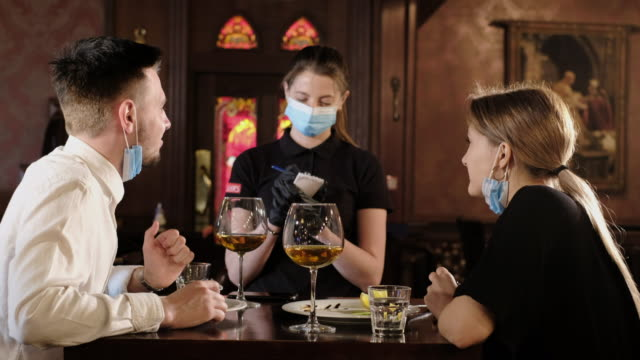 couple eating at bar reopening after quarantine restriction - mask стоковые видео и кадры b-roll