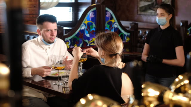 vídeos de stock e filmes b-roll de couple eating at bar reopening after quarantine restriction - covid restaurant
