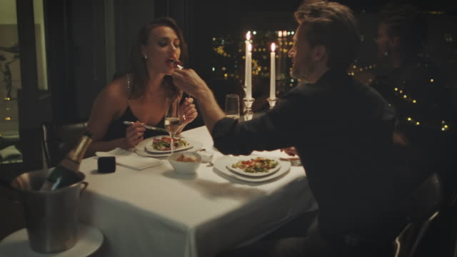 Couple eating dinner A couple sitting at a dining table. They eating their meal and feading each other.   romance stock videos & royalty-free footage
