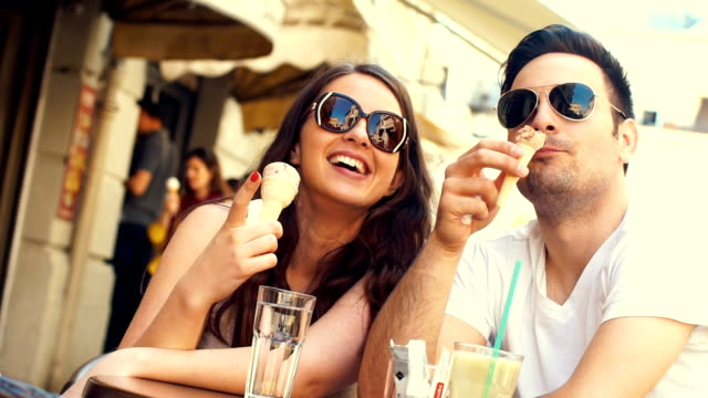 Couple eating ice cream at a cafe slow motion. video