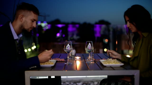 Couple eating pasta in restaurant at evening video