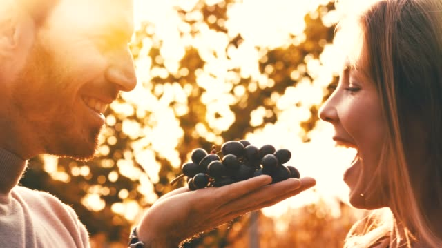 Couple eating red grapes together