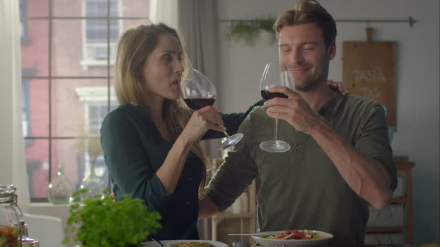 Couple eating self-made food and drinking wine in the kitchen video