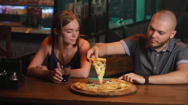 Couple eating unhealthy pizza in a bar