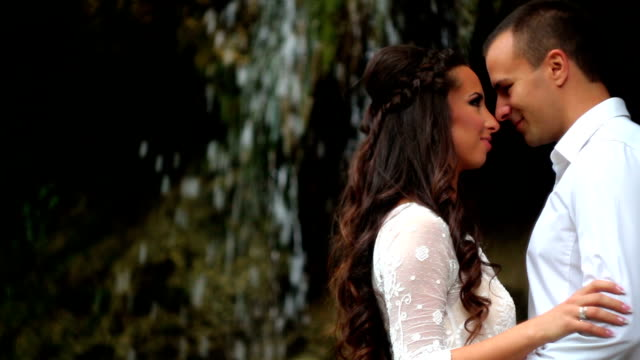 Couple embracing by waterfall video