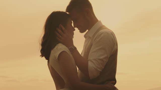 Couple embracing man kissing woman.