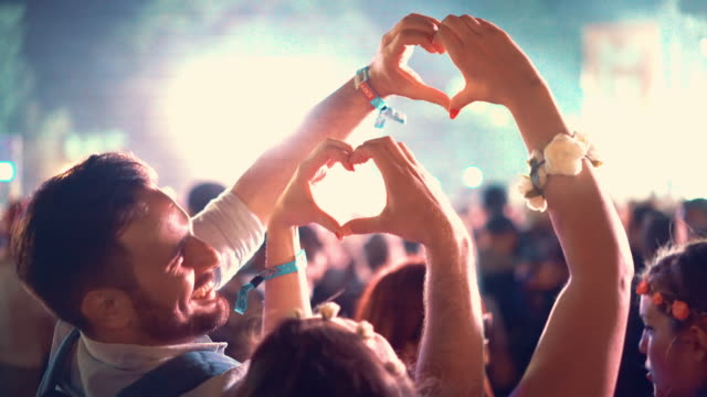 Couple enjoying at a concert, 4k. Closeup rear view of happy mid 20's couple kissing and making heart shaped symbols with their hands at an open air summer concert. There is large blurry crowd in background. 4k video, night shot. party social event stock videos & royalty-free footage