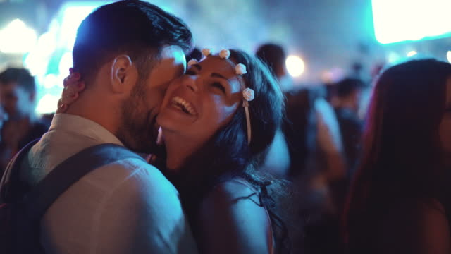 Couple enjoying at a concert, 4k. Closeup rear view of happy mid 20's couple kissing and enjoying open air concert. There is large blurry crowd in background. 4k video, night shot. kissing stock videos & royalty-free footage