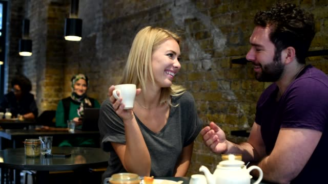 couple enjoying cake and coffee in cafe - incontro romantico video stock e b–roll
