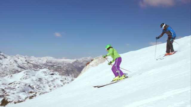 PAN Couple enjoying carving on the sunny ski slope video