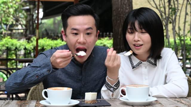 vidéos et rushes de couples appréciant le café avec la femme essayant le cheesecake - tentation
