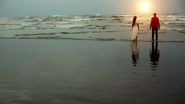 Couple enjoying fresh on tropical sandy beach during sunset time video