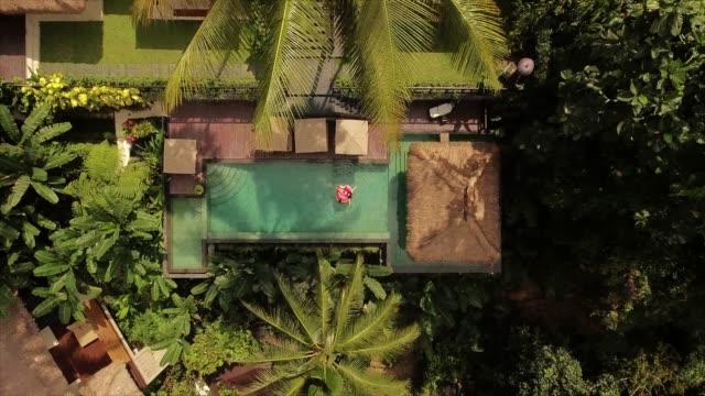 par njuter av semester på luxury resort - inflatable ring bildbanksvideor och videomaterial från bakom kulisserna