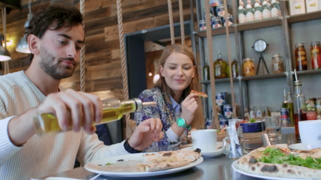 couple enjoying pizza in pizzeria - olio d'oliva video stock e b–roll