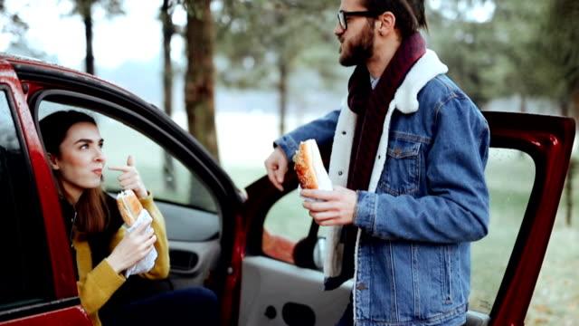 vídeos de stock e filmes b-roll de couple enjoying road trip and lunch break - sanduíche