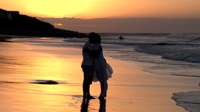 Couple enjoying romantic embrace on the beach in silhouette,South Africa video