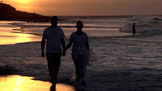 Couple enjoying romantic walk along the beach in silhouette, Cape Town,South Africa video