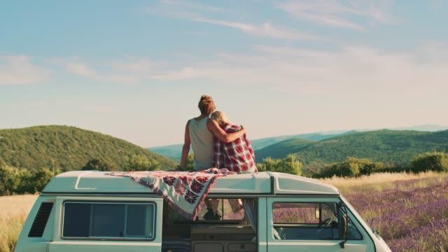 couple enjoying scenery while sitting on van roof - furgone video stock e b–roll