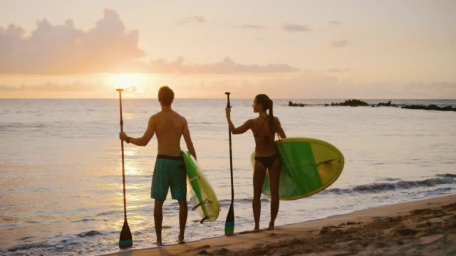 Couple enjoying sunset on the beach with stand up paddle boards