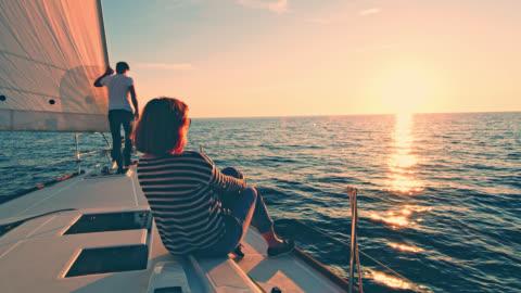vídeos de stock e filmes b-roll de ws couple enjoying the sailing at sunset - admirar a vista