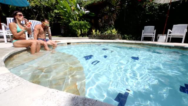 太陽とバリ島でのプライベートヴィラでプールで健康的なフルーツ プレートを楽しんでいるカップル - ヴィラ点の映像素材/bロール
