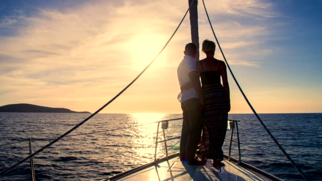 WS Couple Enjoying View From The Bow HD1080p: WIDE ANGLE shot of a silhouette of a couple enjoying the view from the bow of a sailboat sailing on the ocean at sunset. Also available in 4K resolution. yachting stock videos & royalty-free footage