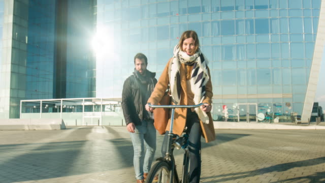 Couple enjoying with bicycle and skating board outdoors video