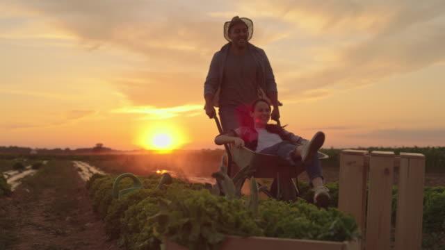SLO MO Couple enjoys the ride with a wheelbarrow