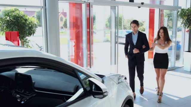 couple entering a car dealership to purchase a car couple entering a car dealership to purchase a car for wife car dealership stock videos & royalty-free footage