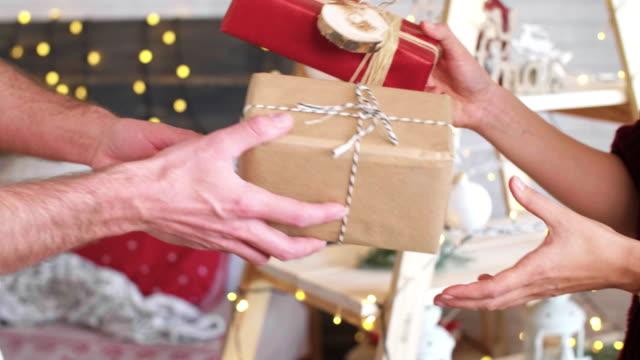 stockvideo's en b-roll-footage met paar uitwisseling van hun kerstcadeaus - uitwisselen