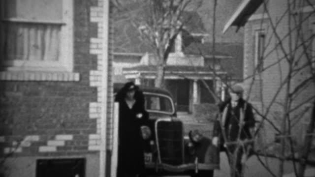 1936: Couple exits Lincoln car enters suburban brick home.