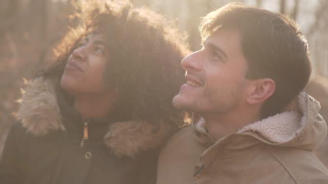 vídeos de stock e filmes b-roll de couple exploring nature on cold winter day - man admires forest